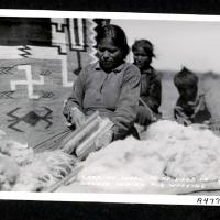 Carding wool to be used in Navajo Indian rug weaving.